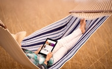 Person with tablet in hammock.